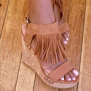 Brown suede wedge sandals with fringes.